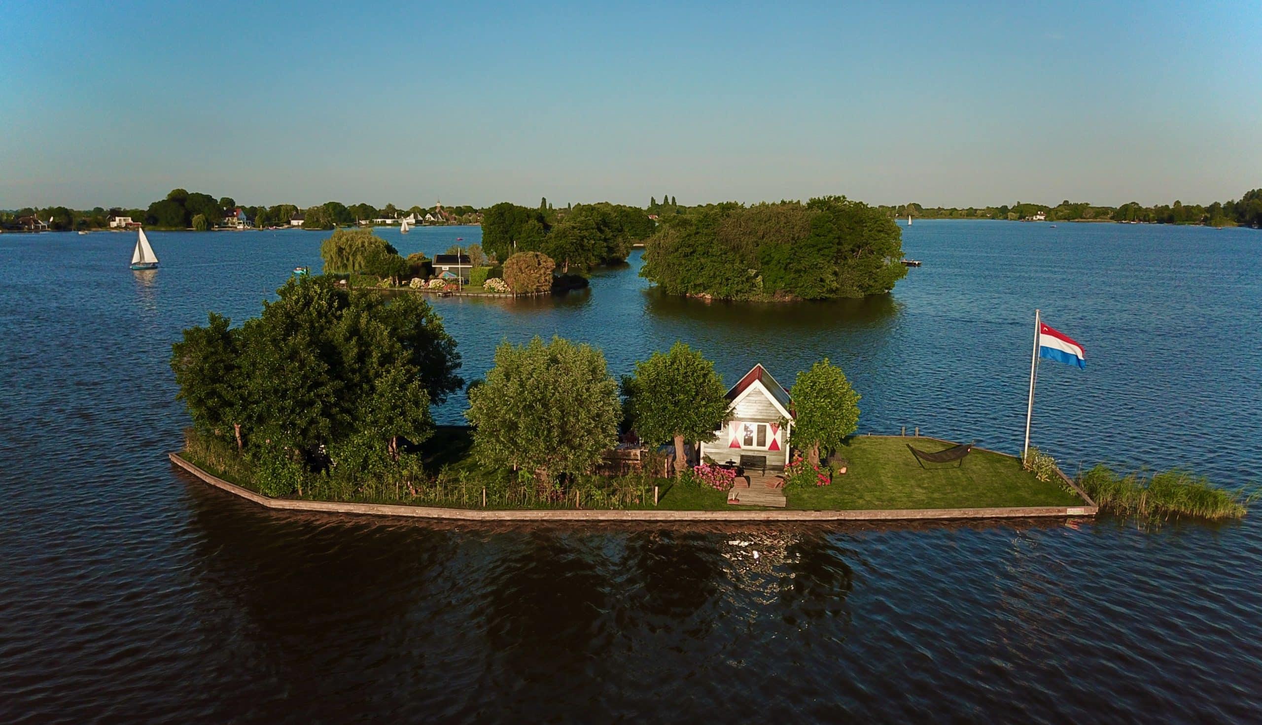 dronebeeld van eiland met huisjes in Reeuwijkse plassen